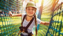 Ein Mädchen kletter durch ein Netz