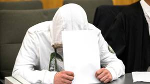 Ein Angeklagter vermummt sich vor den Fotografen. Er ist wegen Vergewaltigung angeklagt