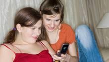 Zwei junge Mädchen mit Handys