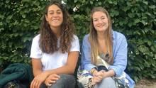 Zwei Mädchen sitzen lächelnd auf einer Bank