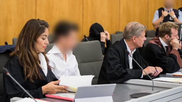 Die Angeklagten (2.v.l, 3.v.l) sitzen im Gerichtssaal neben ihren Anwälten