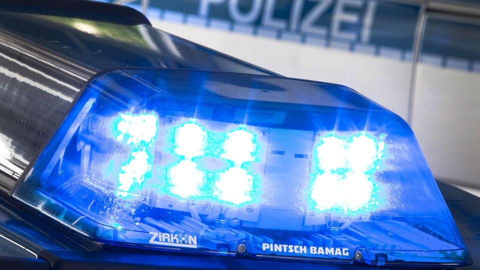 """Auf dem Dach eines Polizeiautos blinkt ein Blaulicht, im Hintergrund steht """"Polizei"""" auf einem anderen Auto"""