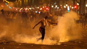 Frankreich, Paris: Ein Mann tritt eine von der Polizei geworfene Tränengasgranate während Ausschreitungen auf der Champs Elysees