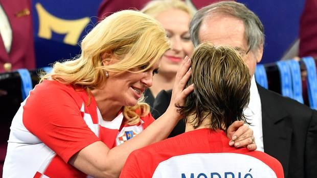 Kolinda Grabar-Kitarovic, die Präsidentin Kroatiens, steht im kroatischen Trikot da und tröstet Luca Modric