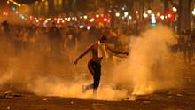 Ein junger Mann hat sich sein T-Shirt vor sein Gesicht gebunden und tritt eine Tränengas-Granate weg