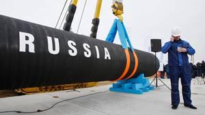 Ein russischer Bauarbeiter telefoniert neben einem Rohrstück für die Gas-Pipeline Nord Stream