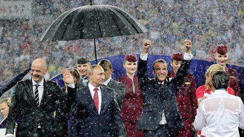 Der russische Präsident Wladimir Putin steht bei der WM-Siegerehrung im strömenden Regen als einziger unter einem Schirm