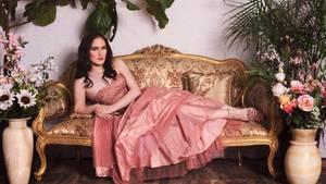 Abby Stein liegt in einem rosa Kleid auf einem Sofa.