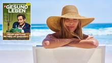 Eine Frau sitzt mit Hut am Badestrand