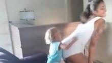 Eine junge Frau in weißem Top und Hotpants twerkt für ihren kleinen Sohn, der auf dem Sofa steht