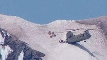Ein Helikopter mit zwei Rotoren setzt mit einem Ende auf einem Hang auf, während die Schnauze in der Luft schwebt.