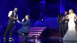 Während ein Mann im Anzug vor einem anderen auf ein Knie heruntergeht, steht Mariah Carey im langen weißen Kleid am Bühnenrand