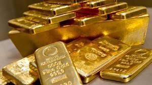 Goldbarren unterschiedlicher Größe liegen gestapelt auf einem Tisch