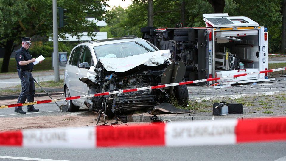 Nahe dem Hamburger Stadtpark liegt ein Rettungswagen nach einem Unfall mit einem weiteren Auto auf der Seite.