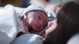 Eine Frau hält ein Neugeborenes nach der Geburt