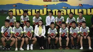 Die zwölf Fußballspieler und ihr Coach auf der Pressekonferenz.