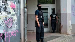 Im Rahmen einer Razzia durchsuchen Berliner Polizisten ein Gebäude