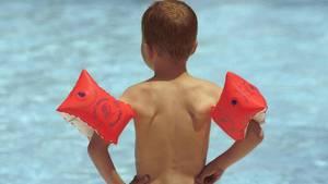 Ein Junge mit Schwimmflügeln steht im Schwimmbad