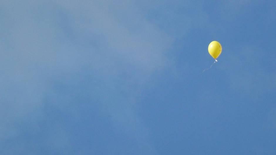 Ein gelber Luftballon schwebt in den Himmel