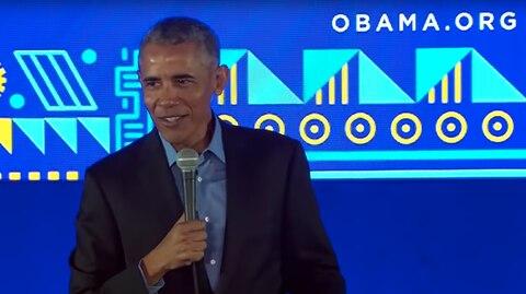 Vor einer blau gemusterten Wand steht Es-US-Präsident Barack Obama auf einer Bühne und hält ein Mikrofon