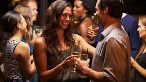 Zwei junge, zufrieden lachende Frauen mit einer Flasche Sekt