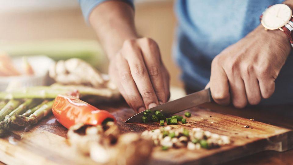 Gemüse wird auf einem Holzbrett geschnitten