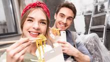 Eine junge Frau mit rotem Haarband und ein junger Mann haben weiße Essensboxen in der einen und Essstäbchen in der anderen Hand