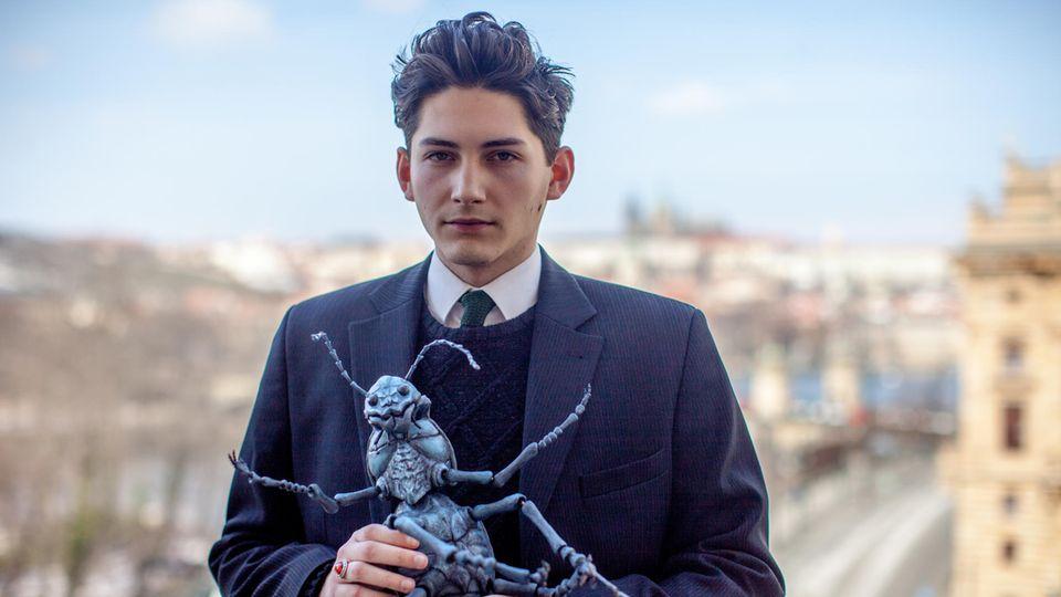 Kafka-Doppelgänger Marek Lentvorsky steht auf der Terrasse des Prager Goethe-Instituts und hält ein Modell des Insekts, in das sich Nutzer von VRwandlung verwandeln.