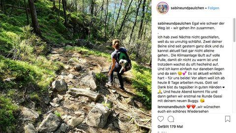 Sabine wandert durch einen Wald und trägt ihren Mops in einem Rucksack auf dem Rücken