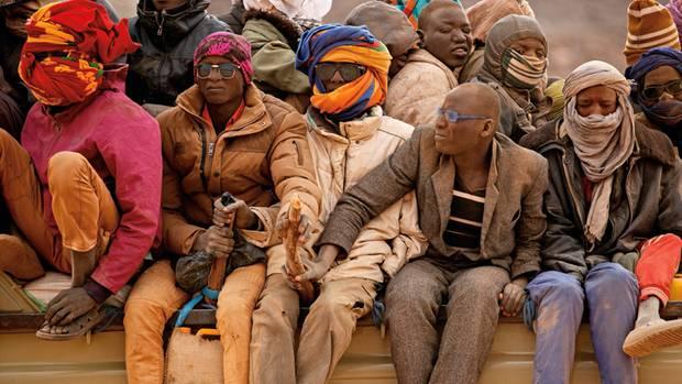 Holzstöcke, festgebunden an der Ladefläche, sind der einzige Schutz der Männer gegen einen Sturz vom Lastwagen auf der Reise durch die Sahara