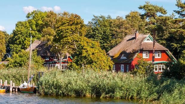 Am Ufer des Prerower Stroms stehen gut erhaltene Reetdachhäuser