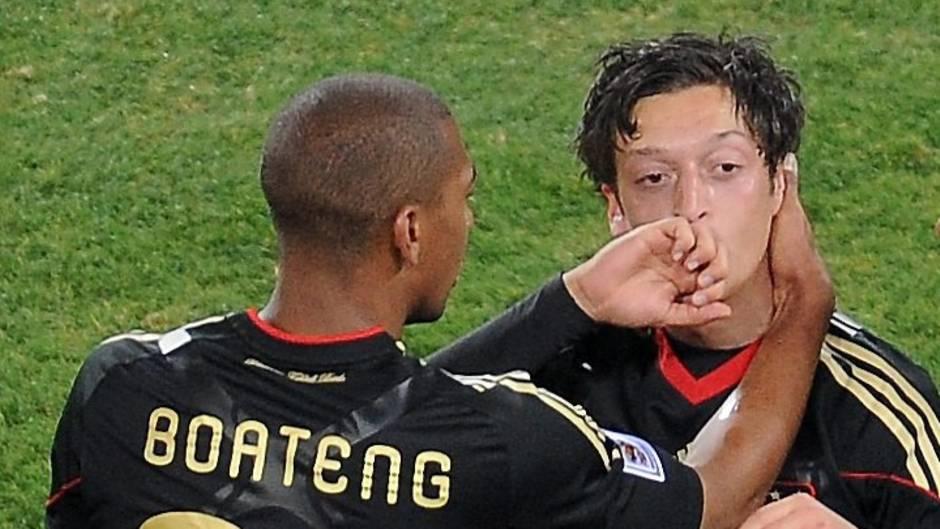 Mesut Özil steht im schwarzen DFB-trikot auf dem Platz und jubelt, Jérôme Boateng beglückwünscht ihn