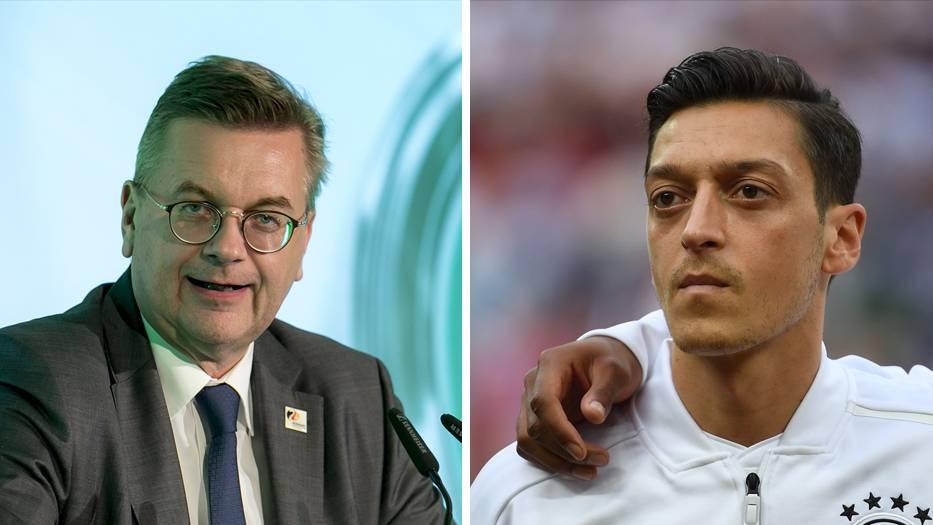 Links steht DFB-Präsident Reinhard Grindel an einem Rednerpult, rechts steht Mesut Özil in DFB-Trainingsjacke auf dem Platz