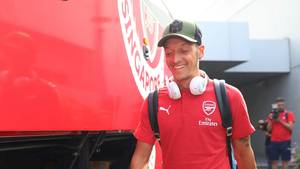 Mit grünem Cap und weißen Kopfhörern um den Hals geht Mesut Özil im roten T-Shirt mit Arsenal-Wappen an einem Bus vorbei