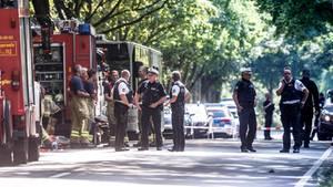 Rettungskräfte stehen nach einem Anschlag auf einen Bus auf der Straße in Lübeck