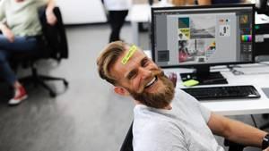 """Ein Mann sitzt lachend vor seinem Schreibtisch, auf seiner Stirn ein Post-it mit """"Be happy"""""""