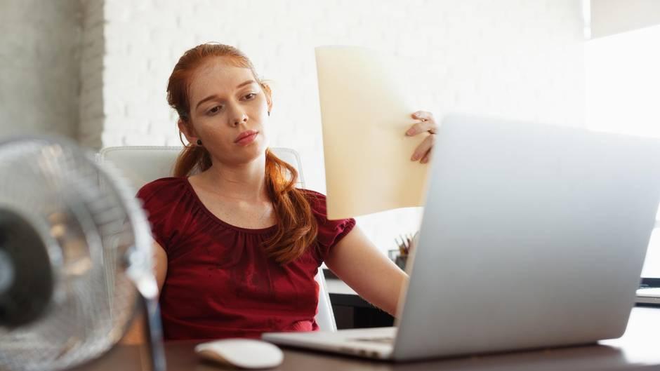 Eine Frau sitzt im Büro und schwitzt