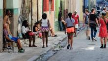 Anwohner sitzen vor ihren Wohnhäuser in einer Straße der Altstadt, während Touristen vorbeigehen.