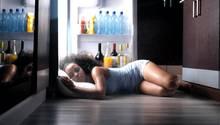 Dachgeschosswohnung: Eine junge Frau schläft vor dem offenen Kühlschrank