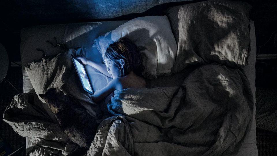 Ein Junge schaut Cartoons im Bett