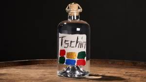 """Tschin Gin  Sie sind ein Purist am Herd, kochen gerne hochwertig aber einfach, reduziert und regional? Dann benötigen sie eine Flasche TSCHIN Gin. Ruedi Käser, Schweizer Obstbrenner, beschränkt sich auf 4 """"Gin-Gewürze"""": Kirschblüten, Waldmeister, Waldbeeren und die Eidgenössische Form des Wacholders, den Reckholder. Der Gin ist kraftvoll, die Flasche schlicht, und das Etikett ein absolutes Unikat - denn jedes wird einzeln (!) von Hand gemalt. Und falls Sie heute doch keine Lust auf Kochen haben - die Flasche TSCHIN passt ideal zur kernigen Brotzeit."""