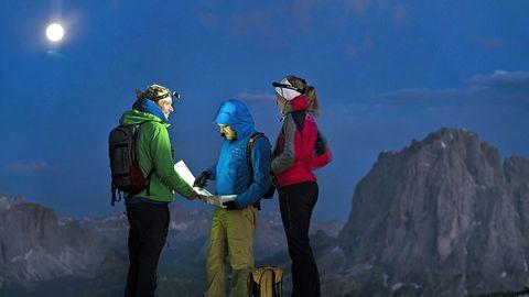 Drei Menschen in Wanderkleidung und mit Kopflampen blicken auf eine Karte. Um sie herum sind Felsen und der Vollmond.