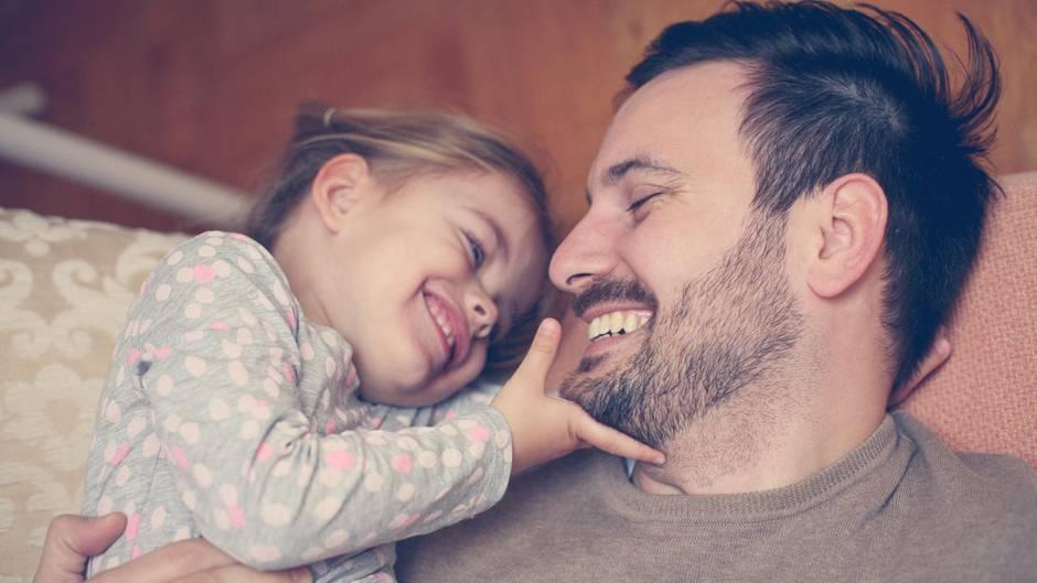 Ein Mädchen krault seinem Vater den Bart
