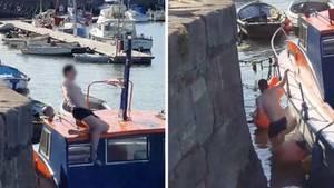Ein junger Mann in Badehose rutscht beim Schritt vom Kai auf die Kajüte eines Bootes aus und stürzt auf das Boot