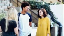 Drei junge Menschen aus unterschiedlichen Kulturen unterhalten sich