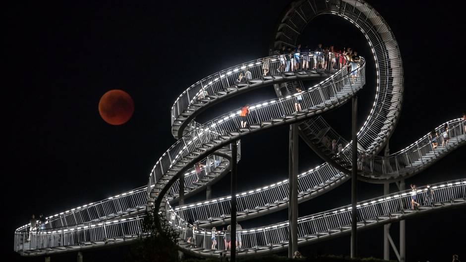 """BeiTemperaturen bis zu 30 Grad haben am Abend unzählige Menschen inDeutschland mit bloßem Auge, Fernglas oder Teleskop das extremseltene Himmelsschauspiel verfolgt - wie hier in Duisburg bei derLandmarke """"Tiger and Turtle""""."""