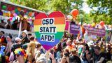 Etliche Teilnehmer waren bunt und glitzernd gekleidet, viele hielten Flaggen in Regenbogenfarben und Transparente in den in den Händen.