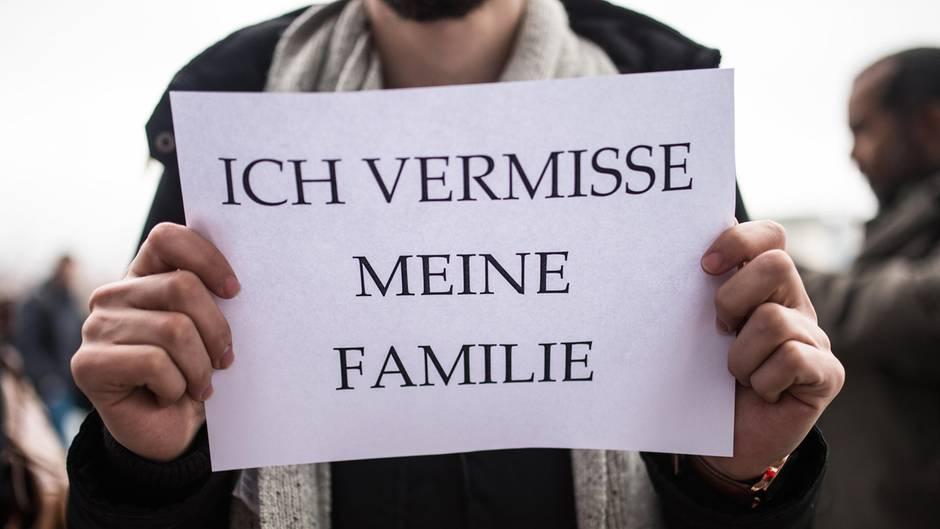 """Ein Mann hält sich ein DinA4-Blatt mit dem Satz """"Ich vermisse meine Familie"""" vor die Brust"""