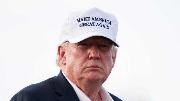 """US-Präsident Donald trump steht im Freien und trägt zu Jackett und offenem Hemd ein weißes Cap mit """"Make America great again"""""""