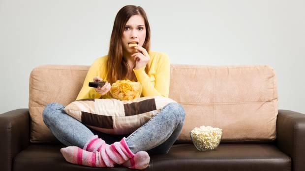 Eine junge Frau sitzt auf dem Sofa und isst Kartoffelchips